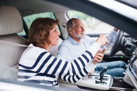 Happy senior couple with smartphone sitting in car, talking.