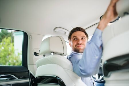 Businessman sitting in brand new car, looking back when driving.