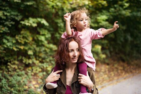 Beautiful young mother with toddler daughter on a walk in autumn forest.
