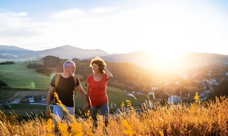 Senior tourist couple travellers hiking in nature at sunset, holding hands.
