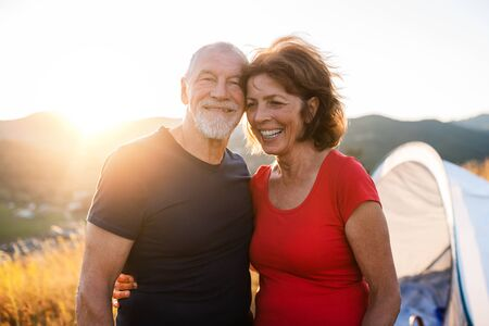 Senior tourist couple standing in nature at sunset, resting.