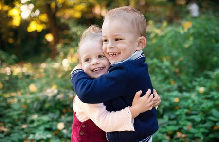 Twin toddler sibling boy and girl standing in autumn forest, hugging.