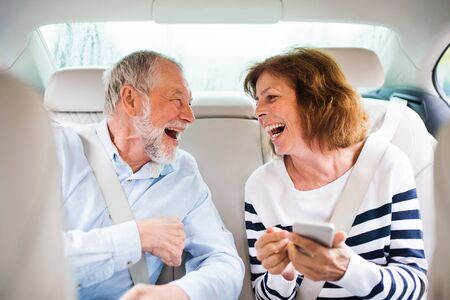 Cheerful senior couple sitting on back seats in car, laughing.