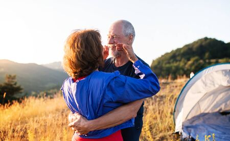 Senior tourist couple in love standing in nature at sunset, hugging.