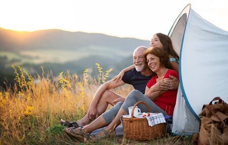 Small girl with grandparents sitting in shelter tent in nature at sunset, resting.