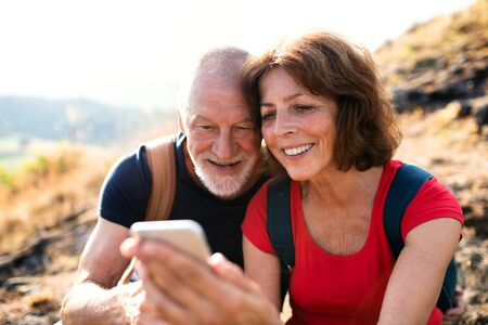 Senior tourist couple hikers in nature, taking selfie.