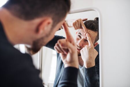A young man indoors looking in the mirror, squeezing a pimple. Stock Photo
