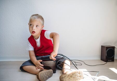 A portrait of down-syndrome school boy sitting on the floor. 免版税图像