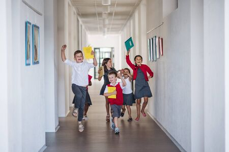 A group of cheerful small school kids in corridor, running and jumping. 版權商用圖片