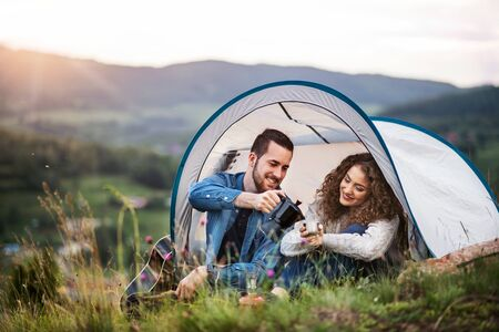 Young tourist couple travellers with tent shelter sitting in nature, drinking coffee.