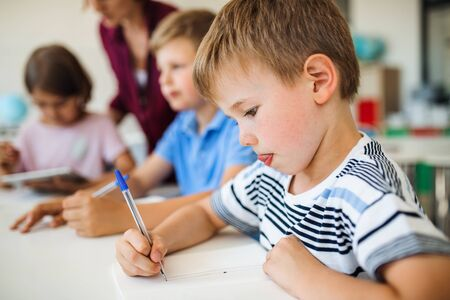 Eine Gruppe kleiner Schulkinder mit Lehrer beim Klassenschreiben.