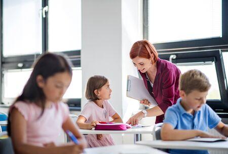 A teacher walking among small school children on the lesson, explaining.