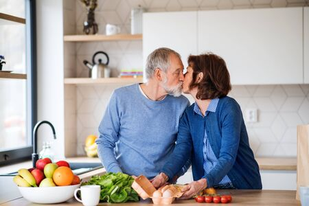 A portrait of senior couple in love indoors at home, kissing when cooking. Фото со стока