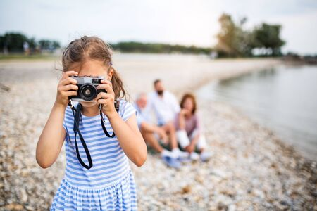 Front view of small girl with camera on a holiday by the lake, taking photos. Stock Photo