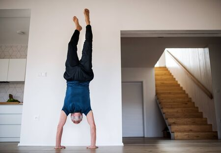 A senior man indoors at home, doing handstand exercise indoors.