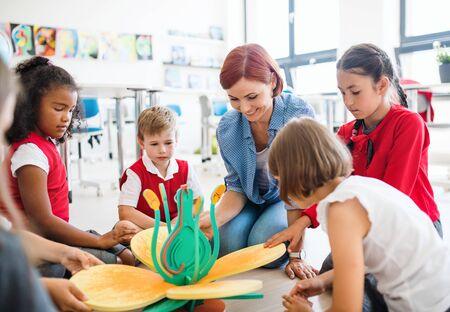 Grupa małych dzieci w wieku szkolnym z nauczycielem siedzącym na podłodze w klasie, uczącym się przedmiotów ścisłych.