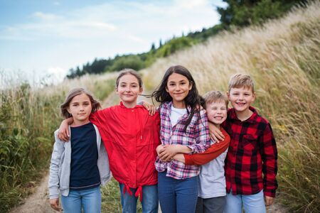 Group of school children standing on field trip in nature, looking at camera. 版權商用圖片