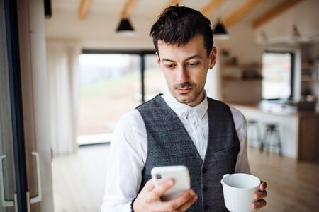 Young man with coffee and smartphone standing indoors at home.
