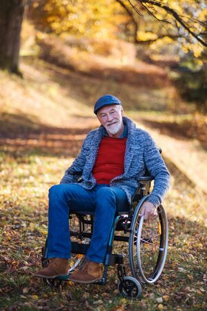 Senior man with wheelchair on walk in nature, looking at camera.