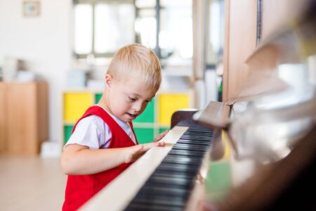 A down-syndrome school boy sitting at school, playing piano.