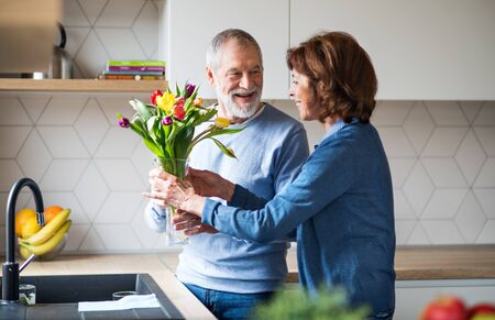 A senior couple in love indoors at home, putting flowers in vase. Фото со стока