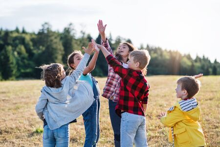 Group of school children standing on field trip in nature, giving high five.