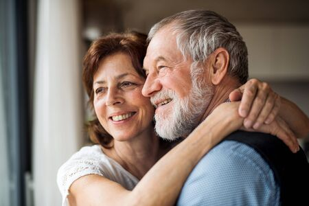 A senior couple indoors at home, looking out of window. Stock fotó