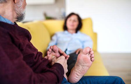 Afectuosa pareja senior enamorada sentada en el sofá en el interior de su casa, relajante Foto de archivo