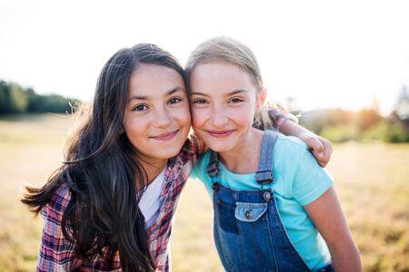Zwei Schulkinder stehen auf Exkursion in der Natur und schauen in die Kamera. Standard-Bild