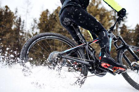 Buik van mountainbiker rijden in de sneeuw buiten in de winter.