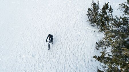 Aerial view of mountain biker riding on snow in forest outdoors in winter. Standard-Bild