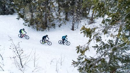 Aerial view of mountain bikers riding on road in forest outdoors in winter.