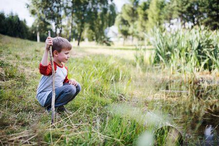 Portrait of school child on field trip in nature, looking at pond. 版權商用圖片
