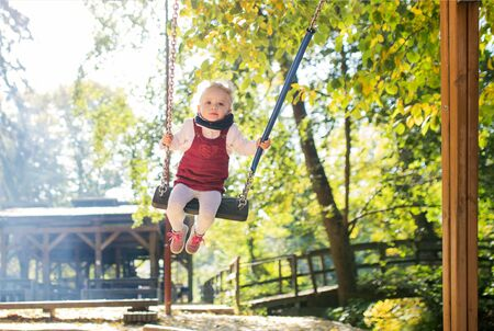 Front view of a small toddler girl on a swing on a playground. Stockfoto