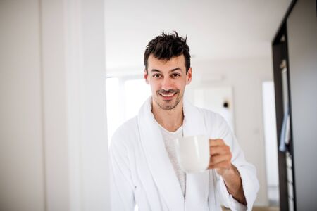 Young man with coffee in the bedroom in the morning.