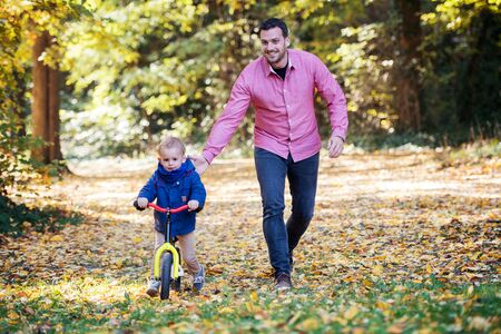 Father and small son with a balance bike on a walk in autumn forest.