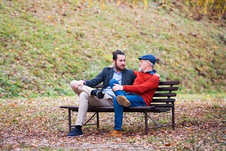 Senior father and his son sitting on bench in nature, talking.