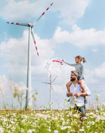 Mature father with small daughter walking on field on wind farm. Stockfoto