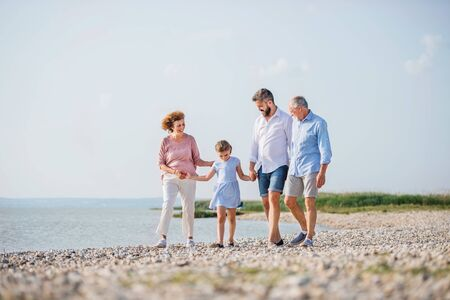 Multigeneration family on a holiday walking by the lake, holding hands. Stockfoto