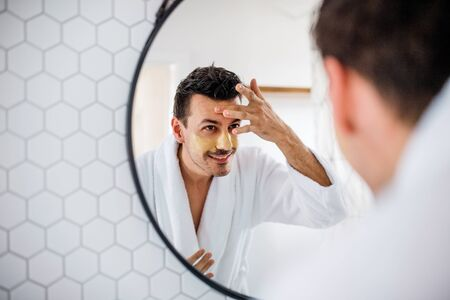 Young man putting mask on face in the bathroom in the morning, daily routine. Stockfoto