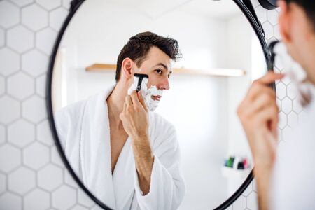 Young man shaving in the bathroom in the morning, daily routine.
