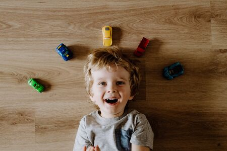 A top view of a toddler boy with toy cars lying on floor at home.