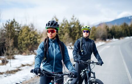 Two mountain bikers resting on road outdoors in winter. Stockfoto