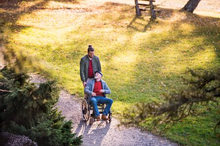 Senior father with wheelchair and his son on walk in nature. Stockfoto