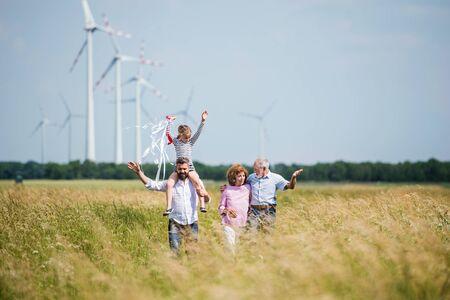 Multigeneration family walking on field on wind farm.