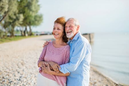 Senior couple on a holiday on a walk by the lake, hugging. Stockfoto