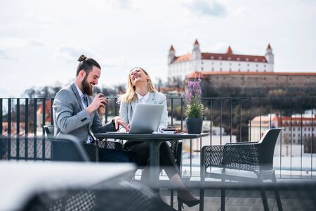 Two young business people with laptop sitting on a terrace outside office, laughing.