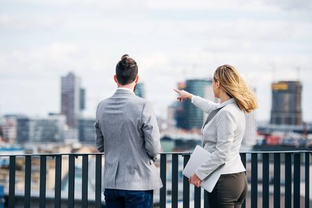 Two young business people with laptop standing on a terrace outside office, talking.