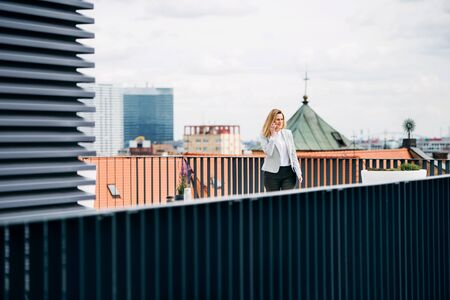 A young businesswoman with smartphone standing on a terrace, working. Stockfoto