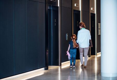 A rear view of businesswoman with small daughter walking in office building.